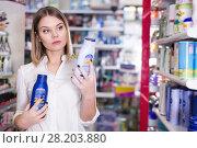 Купить «Serious girl customer looking haircare shampoos», фото № 28203880, снято 31 января 2018 г. (c) Яков Филимонов / Фотобанк Лори