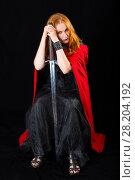 Купить «Young woman wearing in a black long gown and red cloak sitting with knightly sword», фото № 28204192, снято 6 июля 2017 г. (c) Сергей Дубров / Фотобанк Лори
