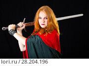 Купить «Red-haired girl wearing in a long black gown and green robe brandishing two-handed sword», фото № 28204196, снято 6 июля 2017 г. (c) Сергей Дубров / Фотобанк Лори