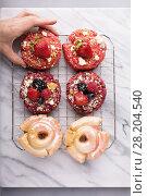 Купить «Variety of donuts on a cooling rack», фото № 28204540, снято 12 марта 2018 г. (c) Елена Веселова / Фотобанк Лори