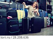 Купить «Female customer choosing travel suitcase», фото № 28208636, снято 18 января 2019 г. (c) Яков Филимонов / Фотобанк Лори