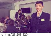team discussing with upset Chinese man foreground. Стоковое фото, фотограф Яков Филимонов / Фотобанк Лори