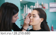 Professional visage artist doing make-up with black eyeliner for beautiful woman. Стоковое видео, видеограф Константин Шишкин / Фотобанк Лори