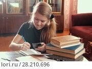 Купить «Cute girl doing homework, writing and holds a smartphone», фото № 28210696, снято 9 марта 2018 г. (c) Константин Шишкин / Фотобанк Лори