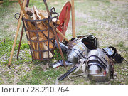 Купить «MOSCOW - JUN 06, 2015: Carapace, sword and shield Roman soldier on the grass near the forged baskets of firewood at the festival Times and epoch: Ancient Rome in Kolomenskoye», фото № 28210764, снято 6 июня 2015 г. (c) Losevsky Pavel / Фотобанк Лори
