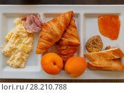 Купить «Millet porridge, ham, croissants, peaches, bread, jam and figs at compartmental dish», фото № 28210788, снято 4 августа 2016 г. (c) Losevsky Pavel / Фотобанк Лори