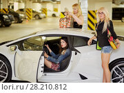 Купить «One woman sits on driver seat and another two stand near modern white car at underground parking», фото № 28210812, снято 2 июня 2016 г. (c) Losevsky Pavel / Фотобанк Лори
