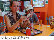 Mother and her son sitting in fast food cafe and drinking soda. Стоковое фото, фотограф Losevsky Pavel / Фотобанк Лори