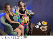 Купить «Two beautiful young women resting with the hookah, focus on the left girl», фото № 28210904, снято 22 апреля 2015 г. (c) Losevsky Pavel / Фотобанк Лори
