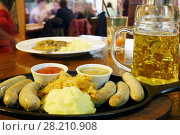 Купить «Yellow fresh hot mashed potatoe, sausages and sauces and beer on table in cafe», фото № 28210908, снято 30 января 2016 г. (c) Losevsky Pavel / Фотобанк Лори
