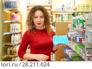 Купить «Pretty woman in red holds sponge for bathing in Goods for Home shop», фото № 28211024, снято 14 октября 2016 г. (c) Losevsky Pavel / Фотобанк Лори