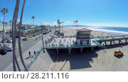 Купить «MANHATTAN BEACH - NOV 02, 2014: People walk by Manhattan Beach Pier along sandy beach at sunny day. Aerial view. Pier was built in 1920.», фото № 28211116, снято 2 ноября 2014 г. (c) Losevsky Pavel / Фотобанк Лори