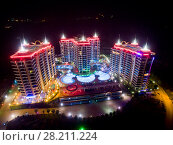 Купить «ALANYA, TURKEY - AUG 16, 2015: Three buildings of apartment complex Azura Park Residence with red light at night, aerial photo», фото № 28211224, снято 16 августа 2015 г. (c) Losevsky Pavel / Фотобанк Лори