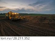 Купить «Machine with illumination for loading of sugar beet are on field in summer evening», фото № 28211352, снято 18 августа 2015 г. (c) Losevsky Pavel / Фотобанк Лори