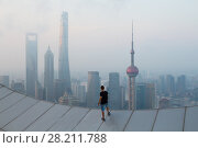Купить «Man stands on roof of skyscraper in foggy Shanghai at early morning, view from White Magnolia Plaza», фото № 28211788, снято 15 августа 2015 г. (c) Losevsky Pavel / Фотобанк Лори