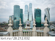 MOSCOW - AUG 3, 2015: Man stands on balcony and looks at Moscow International Business Center at dark night. Years of construction of complex - 1995-2018. Редакционное фото, фотограф Losevsky Pavel / Фотобанк Лори