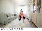 Woman with little baby in hands on her knee in the room. Стоковое фото, фотограф Losevsky Pavel / Фотобанк Лори