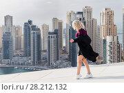 Купить «Young woman goes on rooftop of skyscraper in Dubai Marina area in Dubai, UAE», фото № 28212132, снято 13 января 2017 г. (c) Losevsky Pavel / Фотобанк Лори