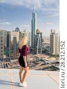Купить «DUBAI, UAE - JAN 13, 2017: Woman on roof looka at Almas Tower, Indigo Tower, Palladium, Lake City Tower, Global Lake View, highway, Every year more than 55 million tourists visit Dubai», фото № 28212152, снято 13 января 2017 г. (c) Losevsky Pavel / Фотобанк Лори