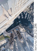 Купить «DUBAI, UAE - JAN 20, 2017: (top view) Roofer legs on Cayan Tower in Dubai Marina area, Cayan is tallest building in world, which is twisted by 90 degrees», фото № 28212296, снято 20 января 2017 г. (c) Losevsky Pavel / Фотобанк Лори