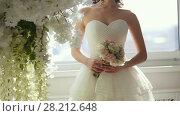 Купить «Attractive model in wedding dress with bride's bouquet», видеоролик № 28212648, снято 25 апреля 2018 г. (c) Константин Шишкин / Фотобанк Лори