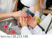 Купить «Woman having manicure in salon», фото № 28213140, снято 2 ноября 2016 г. (c) Яков Филимонов / Фотобанк Лори