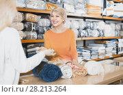 Купить «Mature female seller offering coverlets to young woman in home textile shop», фото № 28213264, снято 15 февраля 2017 г. (c) Яков Филимонов / Фотобанк Лори
