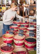 Купить «woman taking dried beans», фото № 28213452, снято 15 ноября 2018 г. (c) Яков Филимонов / Фотобанк Лори