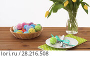 Купить «easter eggs in basket and flowers on served table», видеоролик № 28216508, снято 15 марта 2018 г. (c) Syda Productions / Фотобанк Лори