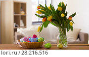 Купить «colored easter eggs in basket and flowers at home», видеоролик № 28216516, снято 16 марта 2018 г. (c) Syda Productions / Фотобанк Лори