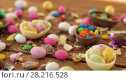 Купить «chocolate easter eggs and drop candies on table», видеоролик № 28216528, снято 15 марта 2018 г. (c) Syda Productions / Фотобанк Лори