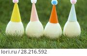 Купить «easter eggs in party caps on artificial grass», видеоролик № 28216592, снято 15 марта 2018 г. (c) Syda Productions / Фотобанк Лори