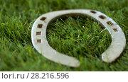 Купить «old horseshoe on artificial grass», видеоролик № 28216596, снято 15 марта 2018 г. (c) Syda Productions / Фотобанк Лори