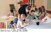 Купить «Smiling boys and girls sitting and teacher helping drawing in classroom», видеоролик № 28216996, снято 7 марта 2018 г. (c) Яков Филимонов / Фотобанк Лори