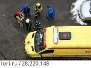 Купить «Сотрудники служб спасения (пожарные и медики) у автомобиля скорой медицинской помощи во дворе жилого дома», эксклюзивное фото № 28220148, снято 23 марта 2018 г. (c) Щеголева Ольга / Фотобанк Лори