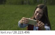 Купить «Woman Sitting In The Park And Doing Selfie», видеоролик № 28223496, снято 25 мая 2017 г. (c) Pavel Biryukov / Фотобанк Лори