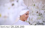 Купить «Smiling muslim bride with bridal make up in flowers», видеоролик № 28226200, снято 27 июня 2019 г. (c) Константин Шишкин / Фотобанк Лори