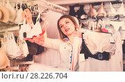 Купить «Positive female shopper choosing bras in shop», фото № 28226704, снято 20 марта 2017 г. (c) Яков Филимонов / Фотобанк Лори