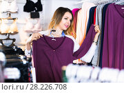 Купить «Female customer is choosing pretty long sleeve shirt», фото № 28226708, снято 20 марта 2017 г. (c) Яков Филимонов / Фотобанк Лори