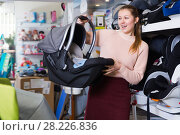 Купить «Smiling female with car cradle for infant», фото № 28226836, снято 19 декабря 2017 г. (c) Яков Филимонов / Фотобанк Лори