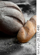 Купить «Freshly baked black bread and French baguette on a black background.», фото № 28227440, снято 21 марта 2018 г. (c) Olesya Tseytlin / Фотобанк Лори