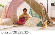 Купить «girl with toy guitar playing in kids tent at home», видеоролик № 28228324, снято 23 февраля 2018 г. (c) Syda Productions / Фотобанк Лори