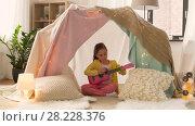 Купить «girl with toy guitar playing in kids tent at home», видеоролик № 28228376, снято 23 февраля 2018 г. (c) Syda Productions / Фотобанк Лори