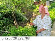 Купить «Женщина поливает огород», эксклюзивное фото № 28228788, снято 19 июня 2010 г. (c) Юрий Морозов / Фотобанк Лори