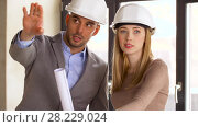 Купить «architects with blueprint and helmets at office», видеоролик № 28229024, снято 4 марта 2018 г. (c) Syda Productions / Фотобанк Лори