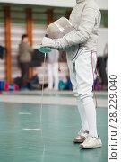 Купить «Participant of the fencing tournament with rapier and protective mask in hands», фото № 28229040, снято 26 марта 2018 г. (c) Константин Шишкин / Фотобанк Лори
