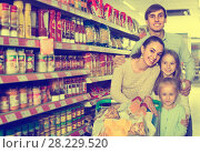Купить «Couple with children buying food in hypermarket», фото № 28229520, снято 21 июля 2018 г. (c) Яков Филимонов / Фотобанк Лори