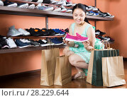Купить «Cheerful woman is choosing sport shoes for jogging», фото № 28229644, снято 10 мая 2017 г. (c) Яков Филимонов / Фотобанк Лори