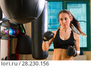 Купить «Strong woman in time of workout at boxer club», фото № 28230156, снято 21 марта 2018 г. (c) Владимир Мельников / Фотобанк Лори