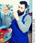 Купить «Worker diagnose broken part of scooter», фото № 28235308, снято 18 июня 2019 г. (c) Яков Филимонов / Фотобанк Лори